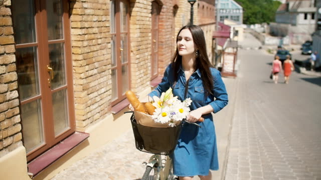 girl walks her bike up the street with flowers in a basket as the sun shines in summertime, slow mo, steadicam shot - cestino della bicicletta video stock e b–roll