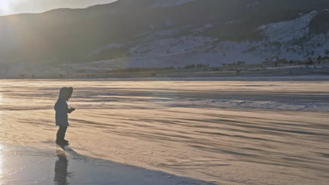 Girl walks on ice. Child on ice in a blizzard. Snow is flying over surface of ice. Snowflakes fly on ice of Lake Baikal. Background view mountain landscape. video