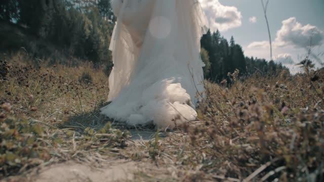 vídeos de stock e filmes b-roll de girl walks through the woods and pulls a white dress on the ground - puxar cabelos