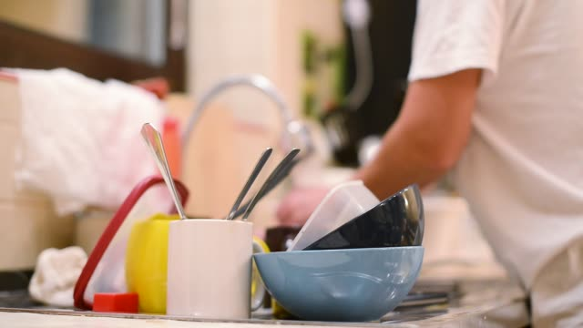 Girl washes dishes out of focus, focusing on a stack of dirty dishes the girl goes to the sink and starts washing dishes. In the focus is dirty dishes and in the background in defocus the girl is washing dishes washing dishes stock videos & royalty-free footage