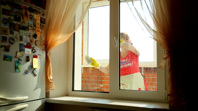 Girl washes the window, view from the front video