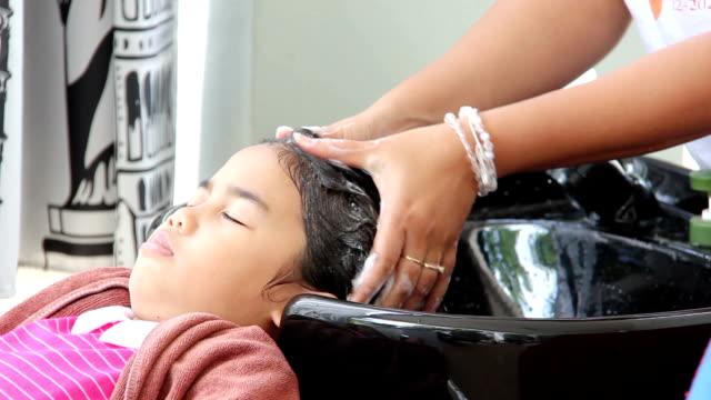 mädchen waschen haare im salon - friseur lockdown stock-videos und b-roll-filmmaterial