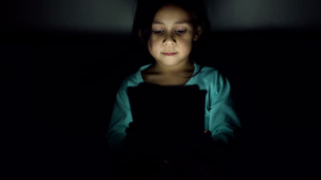 A girl watches cartoons in the tablet late in the evening video