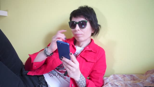 girl watching a video in a smartphone, smiling, rejoices