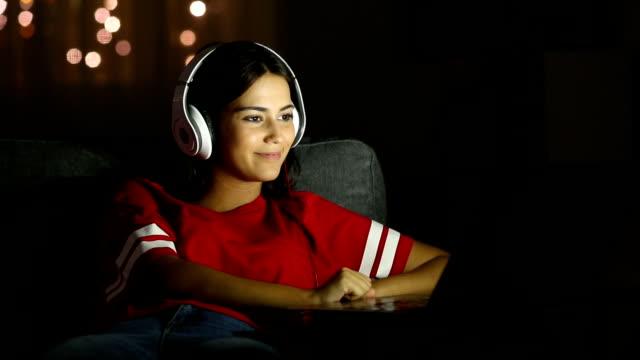 flicka titta på media i en bärbar dator i natt hemma - videor med headphones bildbanksvideor och videomaterial från bakom kulisserna