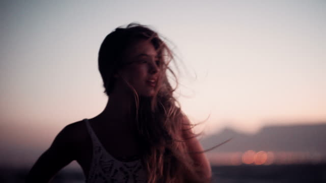 Girl watching the sea on the beach at dusk video