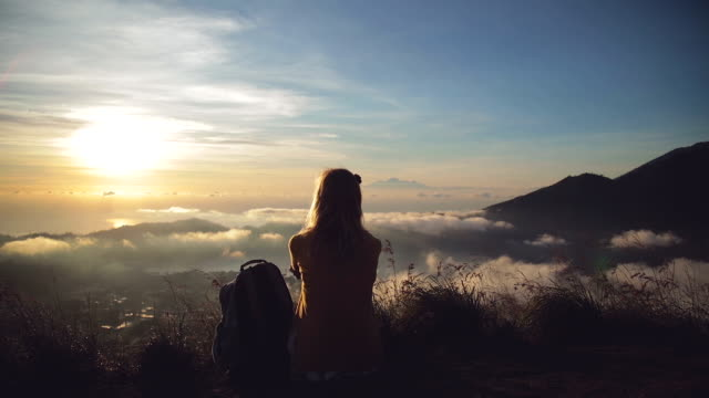 girl watching the sunrise from mount batur, bali - indonesia. - solo una bambina femmina video stock e b–roll