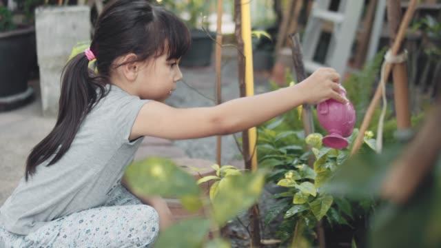 Girl Watering Plants in the Garden Little Girl Watering Plants in a the Garden with a Toy Teapot watering stock videos & royalty-free footage