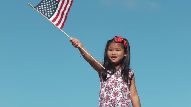 Girl waving American flag in slow motion video