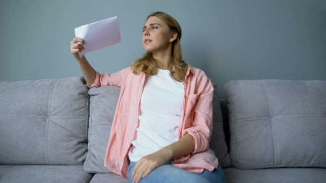 flicka vifta papper sitter på soffan, lider värme, behöver luftkonditioneringen - kvinna ventilationssystem bildbanksvideor och videomaterial från bakom kulisserna