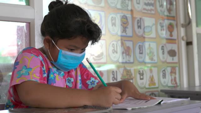 一個戴著面具的女孩在學校做作業。 - back to school 個影片檔及 b 捲影像