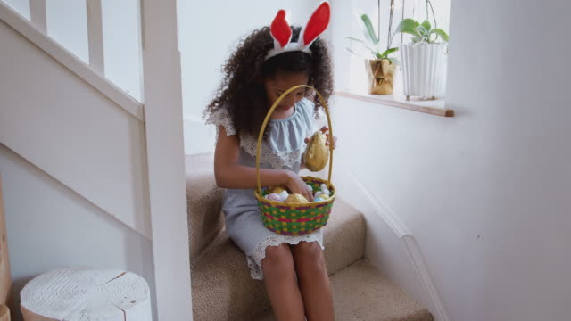 Girl wearing bunny ears sitting on stairs at home eating chocolate egg she has found on Easter egg hunt - shot in slow motion