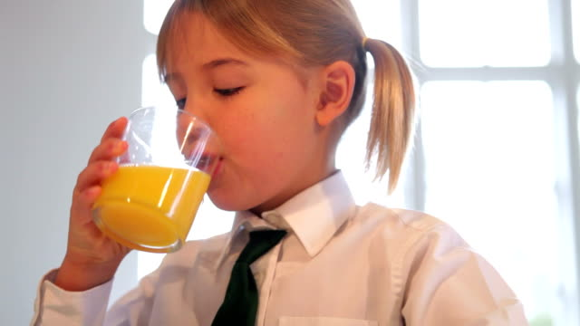 Girl Wearing School Uniform Drinking Glass Of Orange Juice Girl wearing school uniform sitting at kitchen table drinking orange juice.Shot on Canon 5d Mk2 with a frame rate of 30fps orange juice stock videos & royalty-free footage