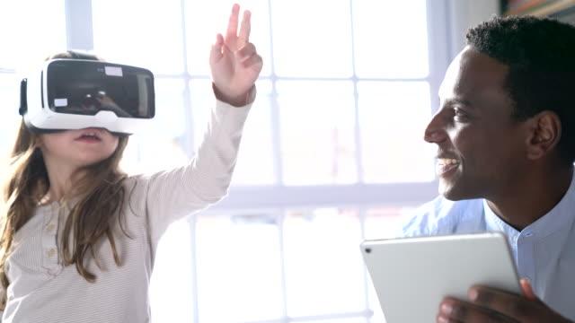Fille qui porte le casque de réalité virtuelle par enseignant - Vidéo