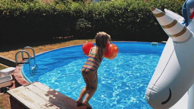 vídeos y material grabado en eventos de stock de chica vistiendo alas de agua y saltando en la piscina - backyard pool