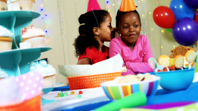 Girl whispering secret to her friend during birthday party 4k video