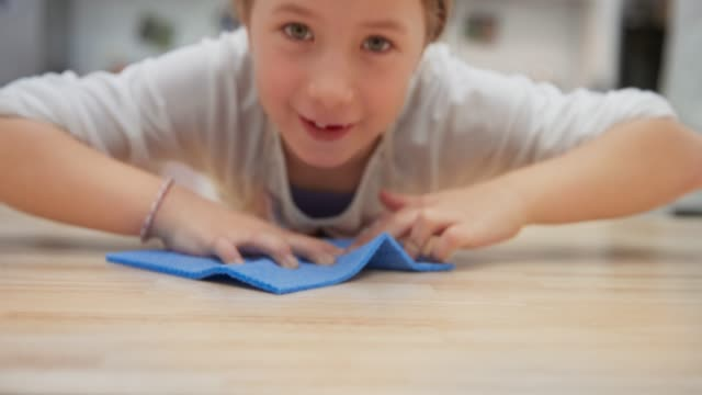 Girl wiping the table with a wet cloth