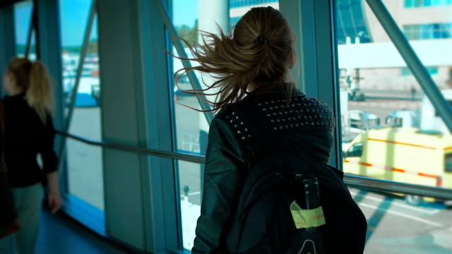 Girl with a backpack goes on the corridor at the airport video