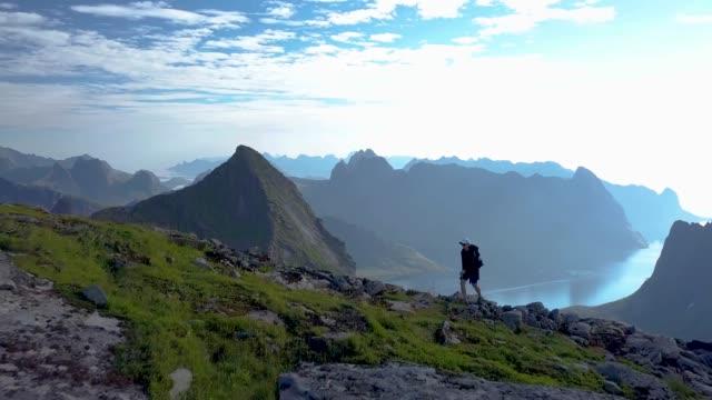vídeos de stock e filmes b-roll de girl with a backpack rises on a mountain ridge - noruega