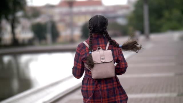 niña con mochila funciona, tarde para el autobús de la noche, nuevo vista, cámara lenta, al aire libre - vídeo