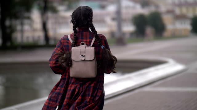 niña con mochila funciona tarde, tarde para el bus, vista de bak, cámara lenta - vídeo