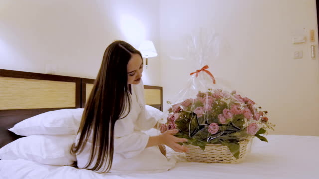 Girl with a basket of flowers. A girl in a white robe, sitting on the bed and unpacking flowers. lamp shade stock videos & royalty-free footage