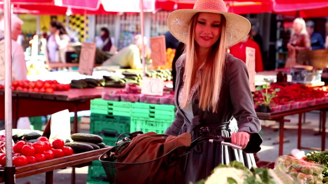 Girl with a bike is walking in the market video