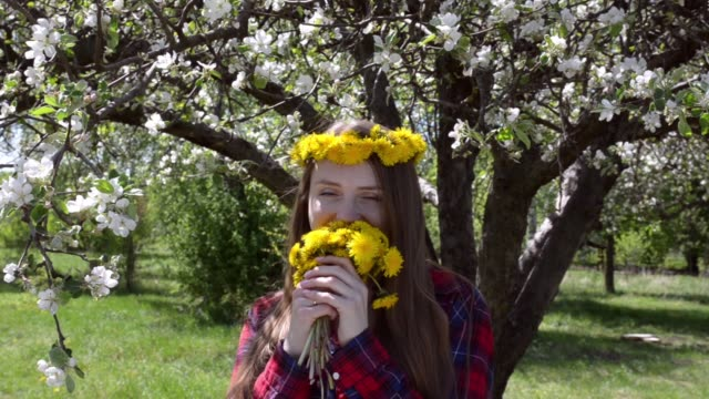 Girl with a bouquet of dandelions and a wreath on her head, enjoying the smell