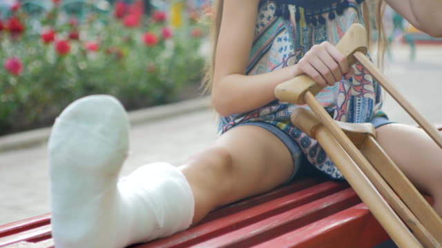 Girl with a broken leg sits on a bench, on the background of a descriptive pad and looks at the smartphone Little girl with crutches at the stair. Back to school crutch stock videos & royalty-free footage