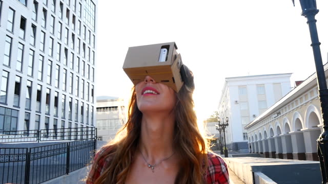 girl with a device of virtual reality in the city - google стоковые видео и кадры b-roll
