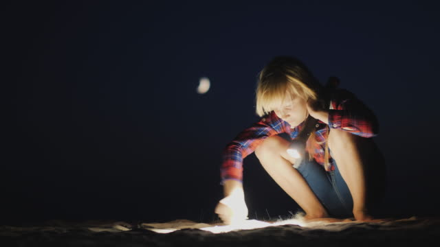 A girl with a flashlight in her hand is looking for something on the beach in the dark. Research and adventure concept A girl with a flashlight in her hand is looking for something on the beach in the dark. Research and adventure concept. flashlight stock videos & royalty-free footage