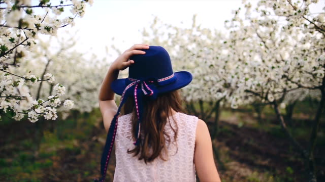 Girl with a scar on arm walking in cherry blossom orchard video