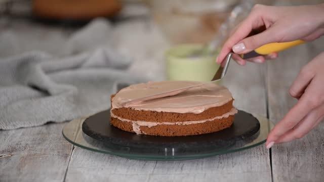 dziewczyna z łopatką rozprowadzając krem na czekoladowy biszkopt - szpatułka przybór do gotowania filmów i materiałów b-roll