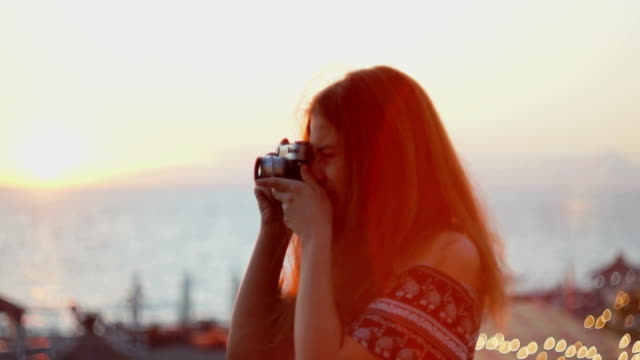 Girl with a vintage camera. Beach, sunset, wind video