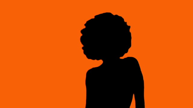 girl with afro dances in silhouette against orange - afro stok videoları ve detay görüntü çekimi