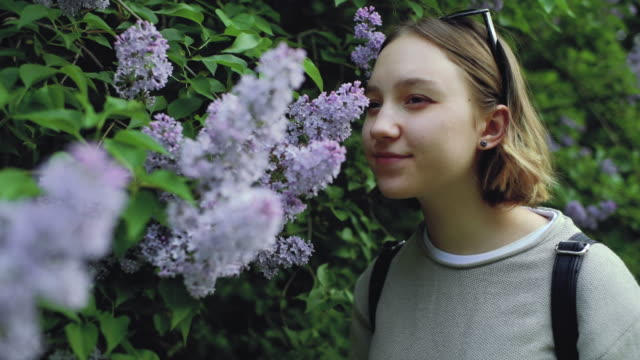 Girl with allergy sneezing and cleaning nose in park near blooming flowers in springtime