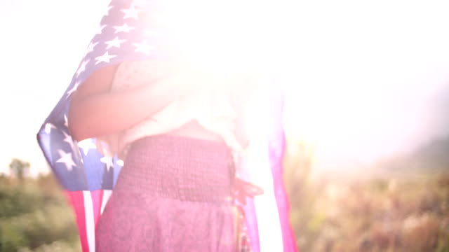 Girl with American flag over her shoulders in natural landscape video