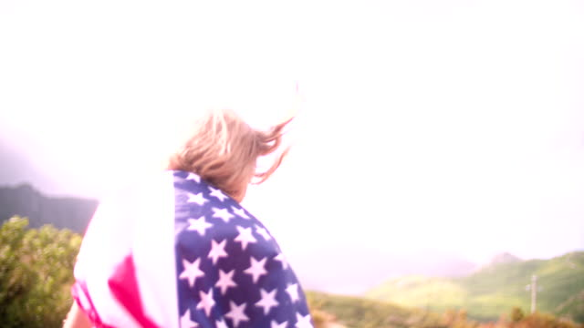 Girl with an American flag over her shoulders in countryside video
