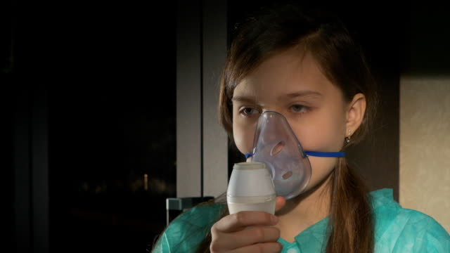 Girl with asthma problems making inhalation with mask on her face video
