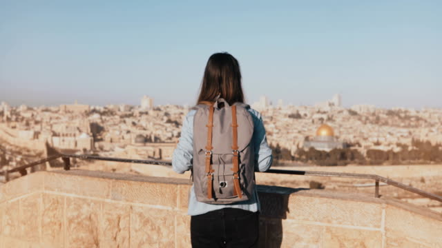 Girl with backpack walks to see old Jerusalem town. Excited European tourist raises hands joyful and happy. Israel. 4K video