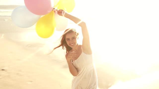 vídeos de stock e filmes b-roll de menina com balões na praia - mulher balões