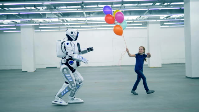 A girl with balloons is dancing and a manlike robot is coming towards her A girl with balloons is dancing and a manlike robot is coming towards her. 4K robot stock videos & royalty-free footage