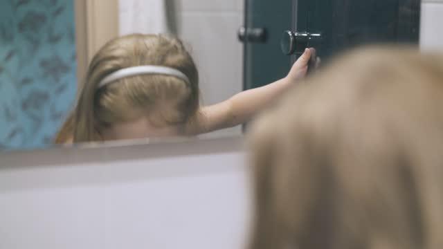 girl with blue eyes gargles throat at mirror in bathroom