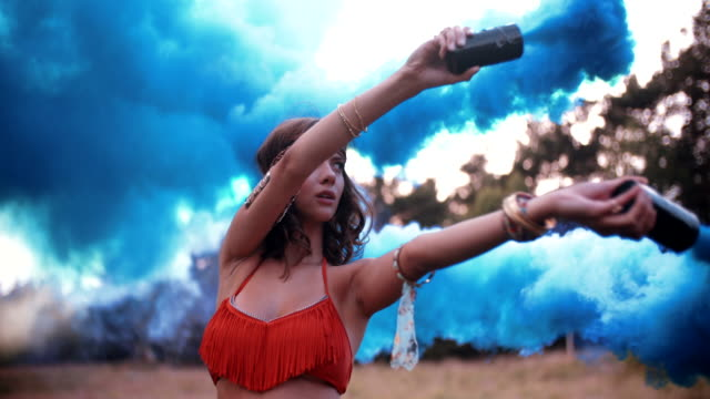 Girl with blue smoke flares in a park video