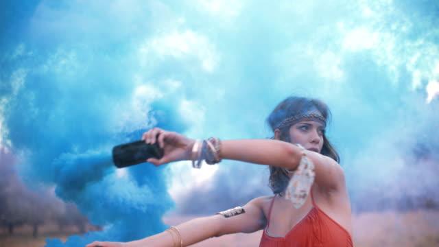 ragazza con fumo blu flare in un parco - hippy video stock e b–roll