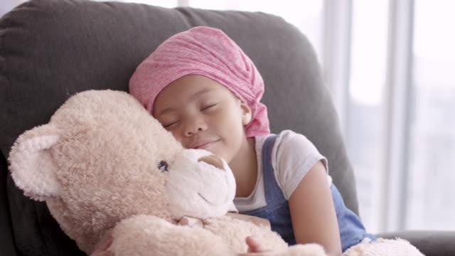 Girl with cancer hugs teddy bear