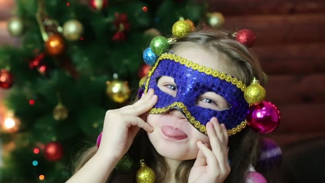 A girl with Christmas garlands on her head in a carnival mask. A little girl with Christmas balls in her hair plays with a carnival mask. mask disguise stock videos & royalty-free footage