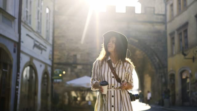 girl with coffe to go exploring old european city at erly morning - occhiata laterale video stock e b–roll