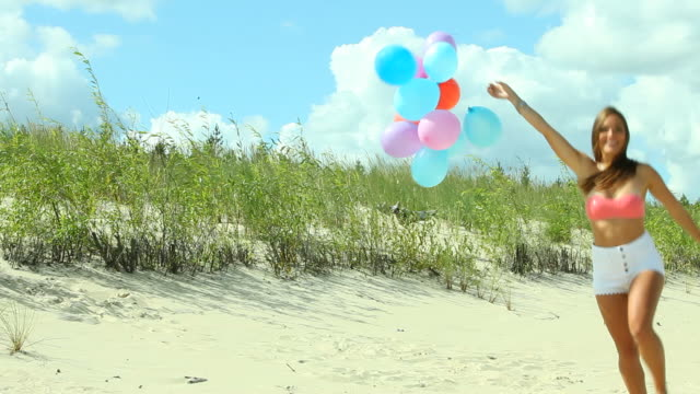 vídeos de stock e filmes b-roll de girl with colorful balloons on beach - mulher balões
