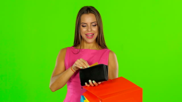 Girl with credit card and shopping bags. Green screen Man pulls out a gold card from her purse, woman presses a card to himself and smiles, young girl opens the purse and pulls out a golden card, on a green background gold card stock videos & royalty-free footage